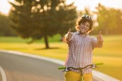 Individuo hermoso en la bici que gesticula los pulgares para arriba imagen de archivo libre de regalías