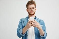 Individuo hermoso joven que frunce el ceño mirando la pantalla del teléfono que practica surf en Internet sobre el fondo blanco Imagenes de archivo