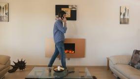 Individuo hermoso que habla en el teléfono en el cuarto elegante con la chimenea eléctrica almacen de video