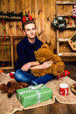 Individuo hermoso que se sienta con un oso del juguete en el cuarto con la Navidad Imagen de archivo
