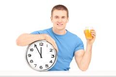 Individuo hermoso que sostiene un reloj y un jugo de pared en una tabla Imágenes de archivo libres de regalías