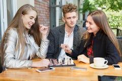 Individuo hermoso y amigas elegantes que juegan a ajedrez en un fondo del café Concepto de los juegos de la inteligencia Foto de archivo libre de regalías