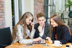 Individuo hermoso y amigas elegantes que juegan a ajedrez en un fondo del café Concepto de los juegos de la inteligencia Fotografía de archivo libre de regalías