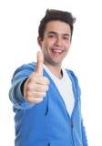 Individuo hispánico en una sudadera con capucha azul que muestra el pulgar para arriba Fotos de archivo libres de regalías
