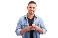 Individuo hispánico que usa un smartphone Foto de archivo libre de regalías