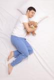 Individuo infantil que duerme con un oso de peluche Fotografía de archivo libre de regalías