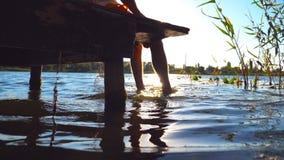 Individuo irreconocible que se sienta al borde de un embarcadero de madera en el lago y pies de balanceo en el agua Hombre joven  metrajes