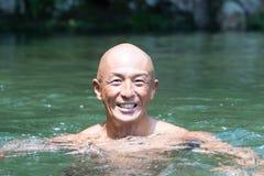 Individuo japonés sonriente de la cabeza calva empapado en agua imagen de archivo