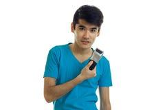 Individuo joven adorable que sostiene podadoras para afeitar y que mira adelante Imagenes de archivo