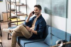 Individuo joven alegre con la barba que se relaja en el sofá usando el teléfono móvil Imagen de archivo