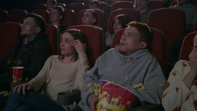 Individuo joven asustado mientras que mira la película de terror en teatro de película almacen de metraje de vídeo