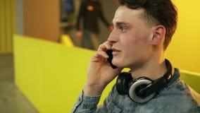 Individuo joven atractivo que habla con alguien en el teléfono Cantidad de la cámara lenta dentro almacen de metraje de vídeo