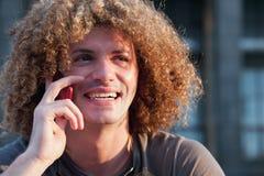 Individuo joven con charla del pelo rizado sobre el teléfono celular Fotografía de archivo