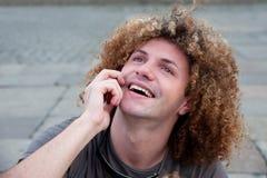 Individuo joven con charla del pelo rizado sobre el teléfono celular Foto de archivo libre de regalías