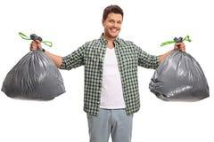 Individuo joven con dos bolsos de basura Fotografía de archivo