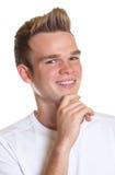 Individuo joven con el pelo rubio que se ríe de la cámara Foto de archivo