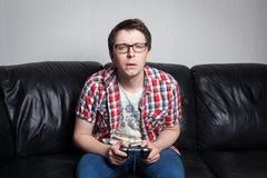 Individuo joven con los vidrios y la camisa roja que juegan a los videojuegos en la palanca de mando, sentándose en un sofá de cu imagen de archivo