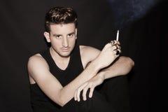 Individuo joven con un cigarro Foto de archivo libre de regalías