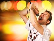 Individuo joven con un micrófono Imagen de archivo libre de regalías