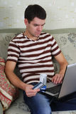 Individuo joven con una computadora portátil Imagenes de archivo