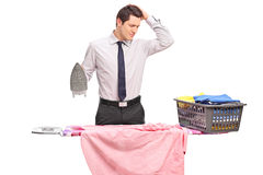 Individuo joven confuso que intenta planchar su ropa Fotos de archivo