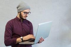 Individuo joven del adolescente que usa el ordenador portátil sobre el fondo blanco del estudio foto de archivo libre de regalías