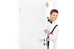 Individuo joven elegante que presenta detrás de una puerta Imagen de archivo