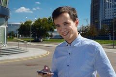 Individuo joven en camisa con un teléfono en sus risas de las manos el día soleado imagenes de archivo