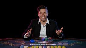 Individuo joven en el casino en línea en la tabla de juego Cierre para arriba almacen de video