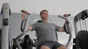 Individuo joven en el gimnasio de la aptitud que hace ejercicios en el simulador metrajes