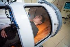 Individuo joven en una cámara hiperbárica, tratamiento del oxígeno fotos de archivo libres de regalías