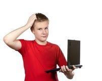 Individuo joven en una camiseta roja con el ordenador portátil en manos en un fondo blanco Imagen de archivo libre de regalías