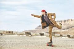 Individuo joven feliz elegante en un casquillo y los basculadores de los pantalones que ruedan abajo un camino de la montaña en u Foto de archivo libre de regalías