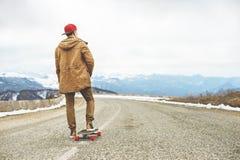 Individuo joven feliz elegante en un casquillo y los basculadores de los pantalones que ruedan abajo un camino de la montaña en u Imagen de archivo