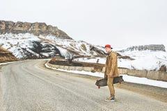 Individuo joven feliz elegante en un casquillo y los basculadores de los pantalones que se retiran un camino de la montaña, un lo Fotografía de archivo libre de regalías
