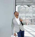Individuo joven feliz que se coloca con el bolso en el aeropuerto Imágenes de archivo libres de regalías