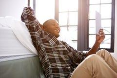 Individuo joven feliz que se sienta comfortablemente en casa usando la tableta digital Imagen de archivo