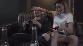 Individuo joven hermoso con su girlfrend que se divierte que juega a los videojuegos que bebe la cerveza con humor excelente en d almacen de video