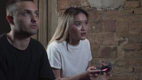 Individuo joven hermoso del retrato con su girlfrend que juega a los videojuegos con en el club moderno del desván Videojuego y o almacen de video