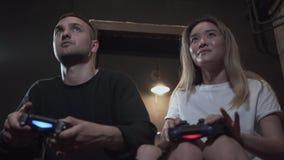 Individuo joven hermoso del retrato con su girlfrend que se divierte que juega a los videojuegos con humor excelente en club mode almacen de video