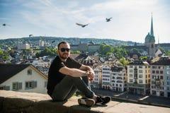 Individuo joven hermoso sentarse en el parque de la ciudad con una opinión de la ciudad en Zurich, Suiza fotografía de archivo libre de regalías