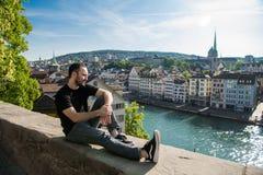 Individuo joven hermoso sentarse en el parque de la ciudad con una opinión de la ciudad en Zurich, Suiza imagen de archivo libre de regalías