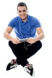 Individuo joven que disfruta de música y que usa la PC de la tableta Fotos de archivo