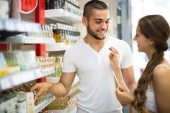Individuo joven que elige perfume en la tienda Imagenes de archivo
