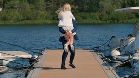 Individuo joven que gira a su novia en el embarcadero metrajes