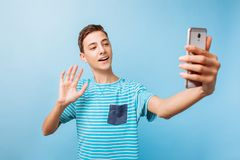 Individuo joven que habla charla video en línea, en el teléfono en el estudio foto de archivo