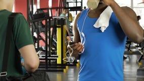 Individuo joven que habla con el amigo en el gimnasio, cóctel de consumición de la proteína, mostrando el bíceps metrajes