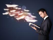 Individuo joven que lee un libro con las hojas de vuelo que salen de BO Fotografía de archivo