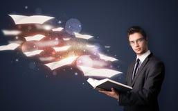 Individuo joven que lee un libro con las hojas de vuelo que salen de BO Fotos de archivo