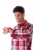 Individuo joven que mira su reloj aislado en el fondo blanco Foto de archivo libre de regalías